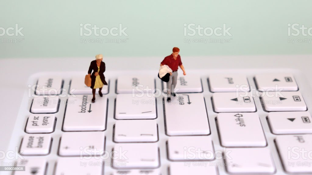 A miniature man walking on top of an enter key and a miniature woman walking on top of a backspace key. The male and female employment gap concept. stock photo