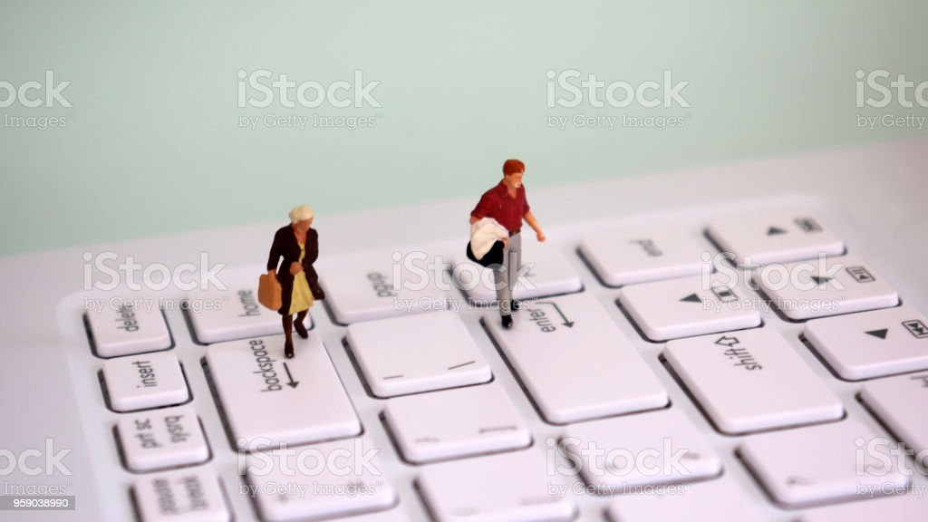 A miniature man walking on top of an enter key and a miniature woman walking on top of a backspace key. A gender discrimination concept. stock photo