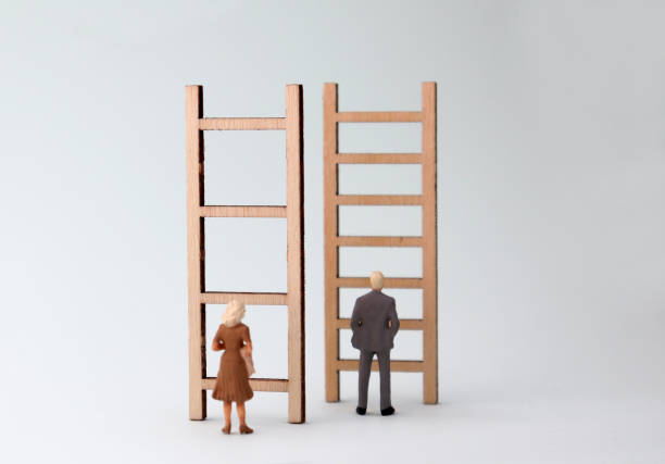 Miniature men and women standing in front of different ladders. The concept of gender promotion discrimination in the workplace. Miniature men and women standing in front of different ladders. The concept of gender promotion discrimination in the workplace. discriminatory stock pictures, royalty-free photos & images