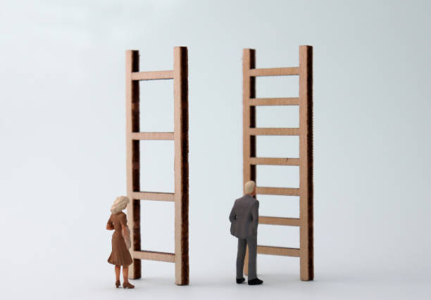 Miniature men and women standing in front of different ladders. The standard concepts that are discriminatory against men and women in their work. Miniature men and women standing in front of different ladders. The standard concepts that are discriminatory against men and women in their work. discriminatory stock pictures, royalty-free photos & images