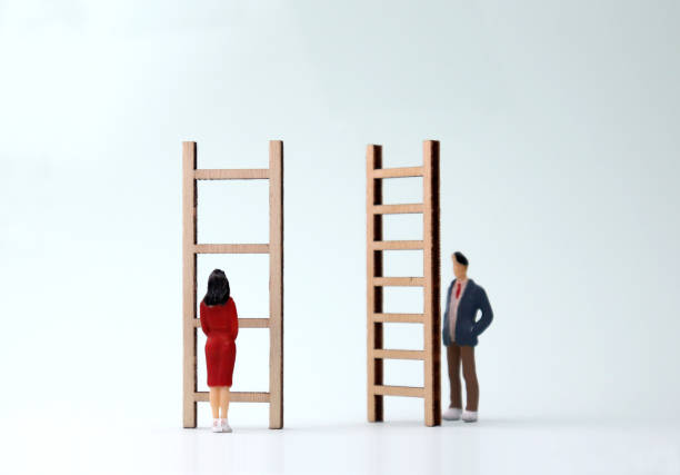 Miniature men and women standing in front of different ladders. The concept of gender differentiation between promotion and employment. Miniature men and women standing in front of different ladders. The concept of gender differentiation between promotion and employment. discriminatory stock pictures, royalty-free photos & images