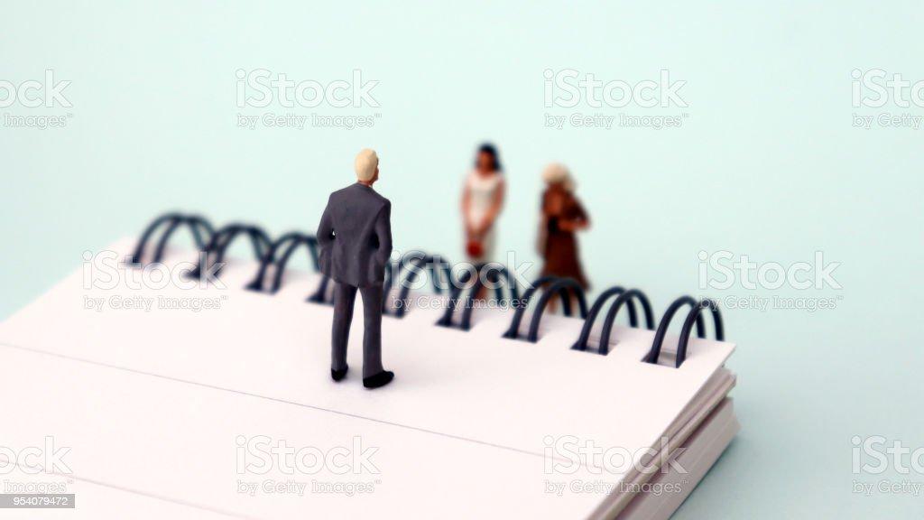 Miniatur-Männer und Frauen stehen auf einem offenen Notebook. Der Begriff der Diskriminierung am Arbeitsplatz aufgrund des Geschlechts. – Foto