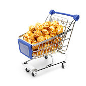 Miniature metal shopping cart filled with the golden sweet popcorn on a white background