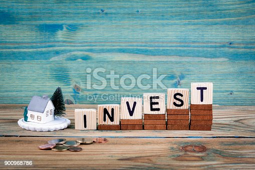 istock miniature model of house and wooden letter text: invest 900968786