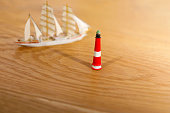 Training ship Gorch Fock sailing around a lighthouse on hardwood floor