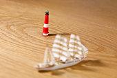 Training ship Gorch Fock sailing around a lighthouse on hardwood floor