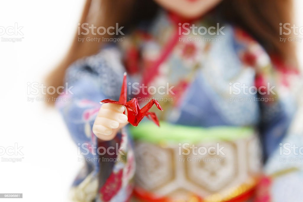 Miniature origami bird and a Japanese doll in kimono royalty-free stock photo