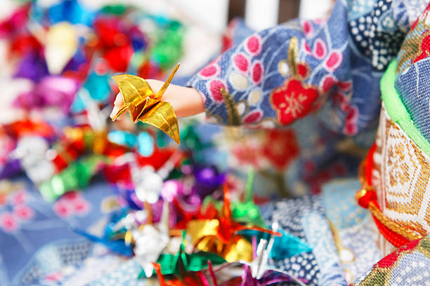 Miniature origami birds and a Japanese doll stock photo