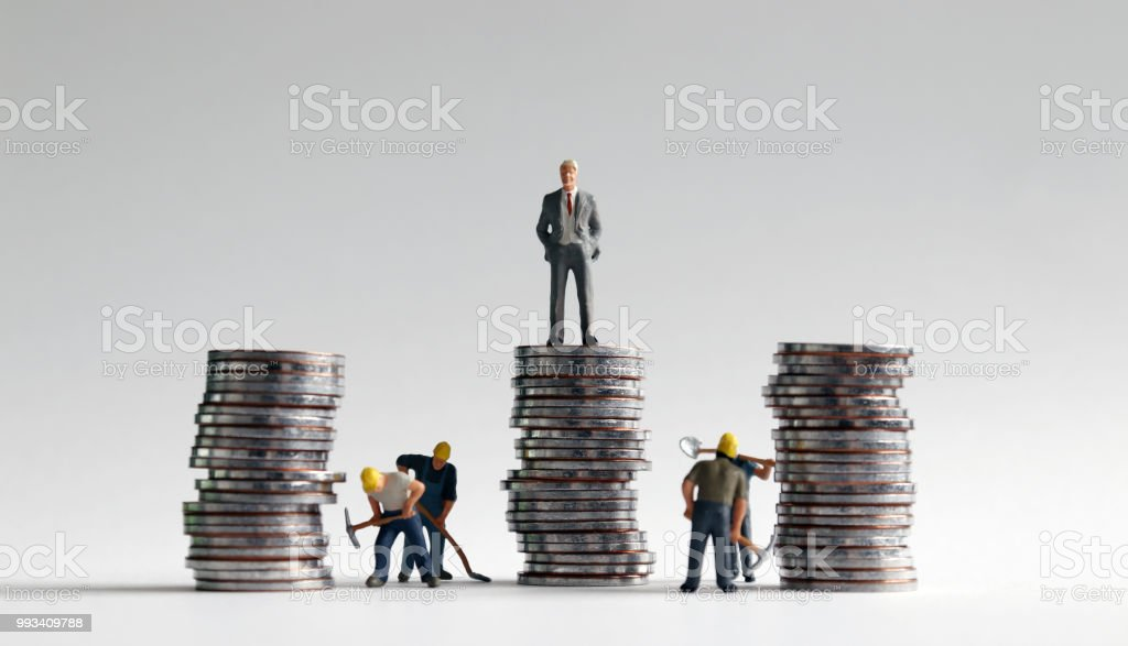 Miniature people and three pile of coins. stock photo