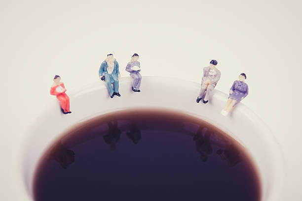 miniature people business team sitting on white coffee cup stock photo