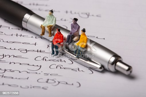 Miniature people figurines sit on a pen which is on a page of hand written words
