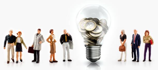 微型人在前面一個燈泡與歐元硬幣內 - 公仔 個照片及圖片檔