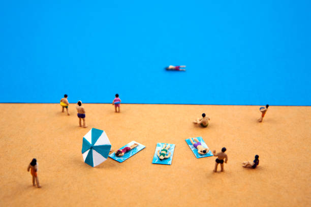 miniature people in the summer beach - figurine stock photos and pictures