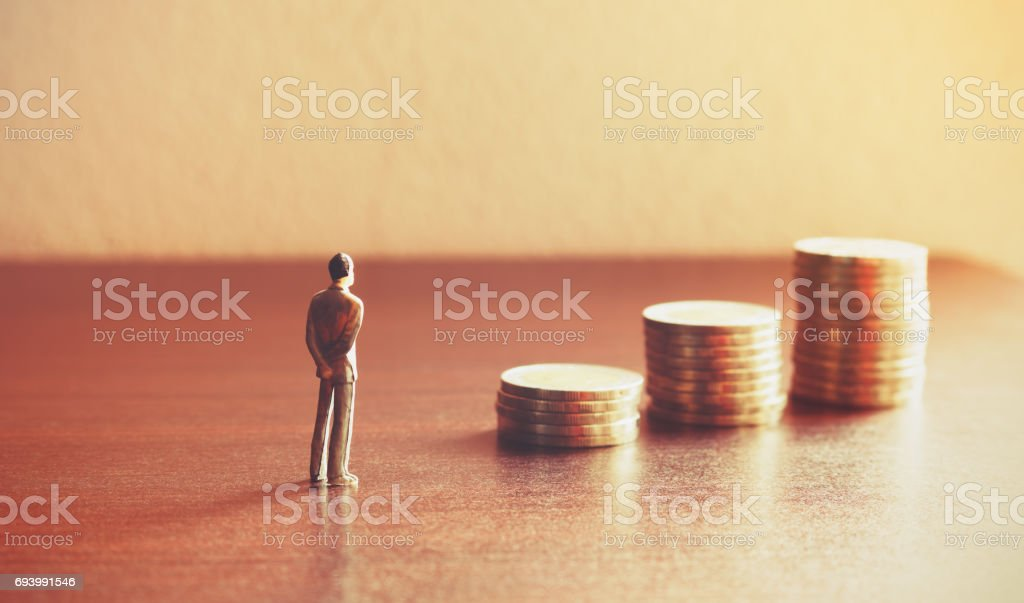 Miniature people looking future with stack coin about financial and money savings concept. foto stock royalty-free