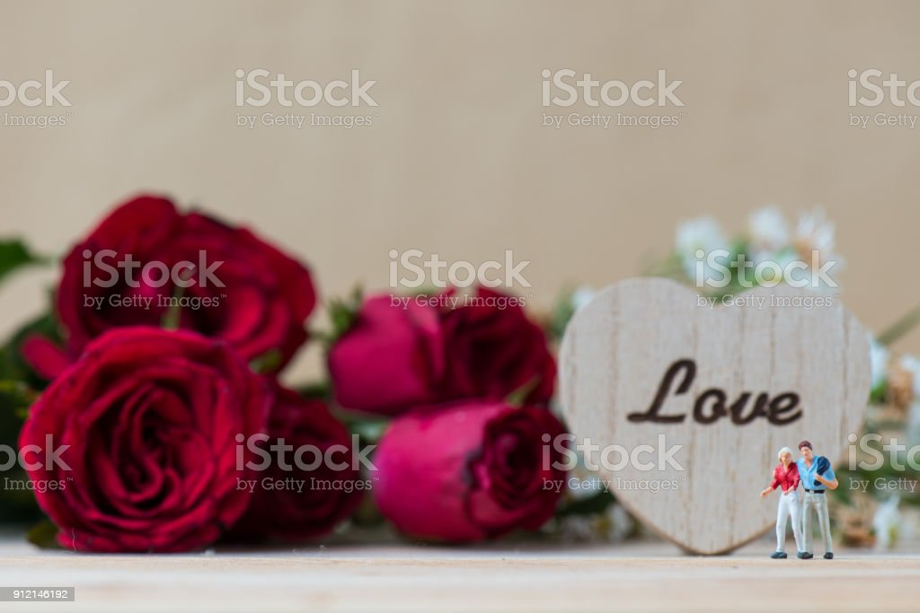 miniature people. lover with the red rose flower and The carved word...