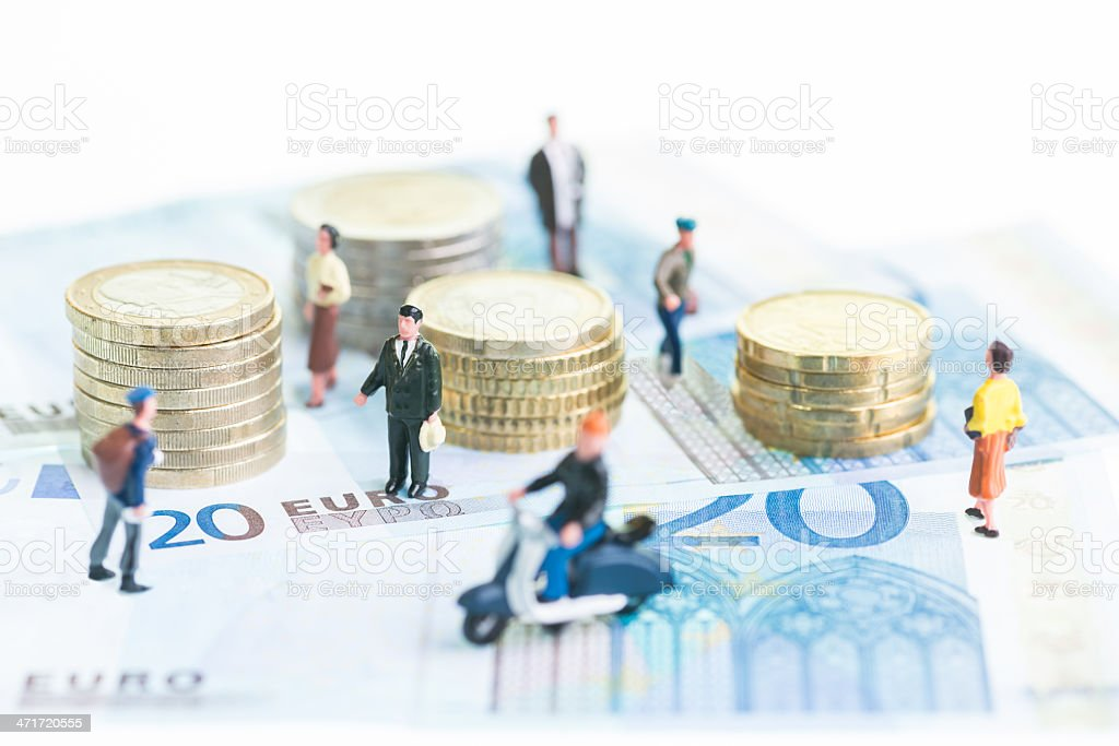 Miniature people on Euro banknotes and coins stock photo