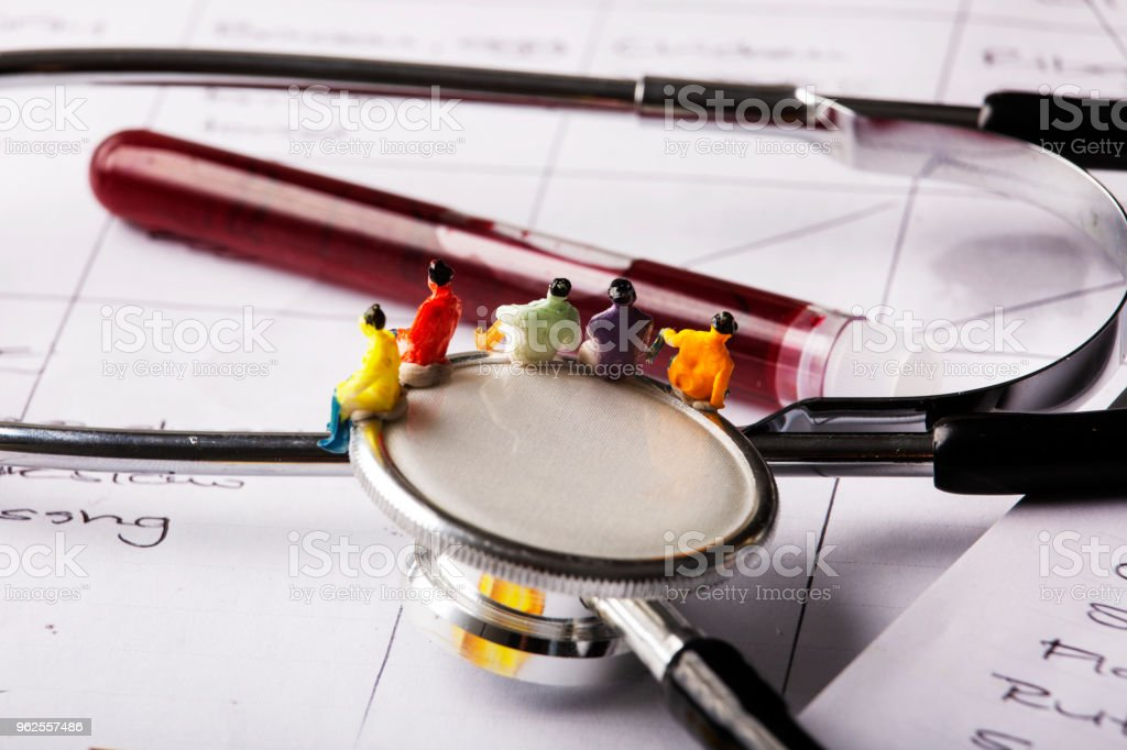 Miniature people sit on syringe looking at a test tube with blood...