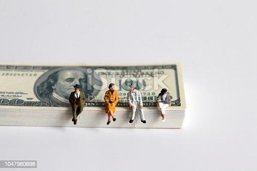 Miniature people sitting on a pile of bills.