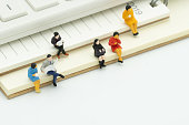 Miniature people sitting on Note Book placed white background. meeting or Discussion using as background business concept with copy space and white space for your text or  design.