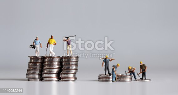 Miniature people standing on a pile of coins. A concept of income disparity.