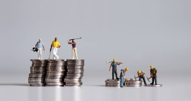 Miniature people standing on a pile of coins. A concept of income disparity. Miniature people standing on a pile of coins. A concept of income disparity. unbalanced stock pictures, royalty-free photos & images