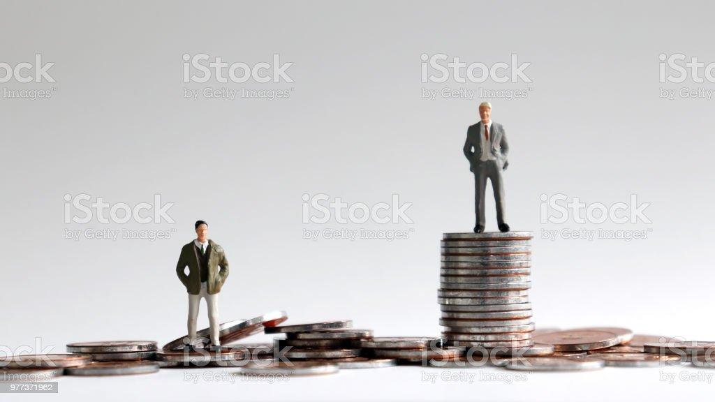 Miniature people standing on a pile of coins. - Zbiór zdjęć royalty-free (Bieda - Problem społeczny)