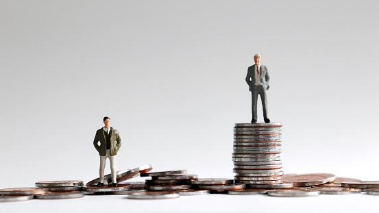 Miniature People Standing On A Pile Of Coins - zdjęcia stockowe i więcej obrazów Bieda - Problem społeczny