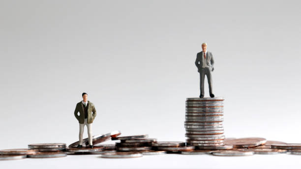 Miniature people standing on a pile of coins. Miniature people standing on a pile of coins. unbalanced stock pictures, royalty-free photos & images