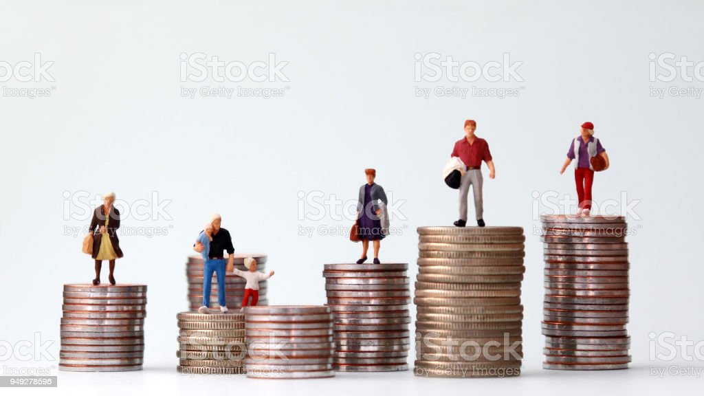 Miniature people standing on piles of different heights of coins. The concepts of person and wealth. stock photo