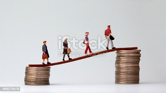 513121118istockphoto Miniature people walking from low to high pile of coins. The concept of the gap between the rich and the poor. 949278476