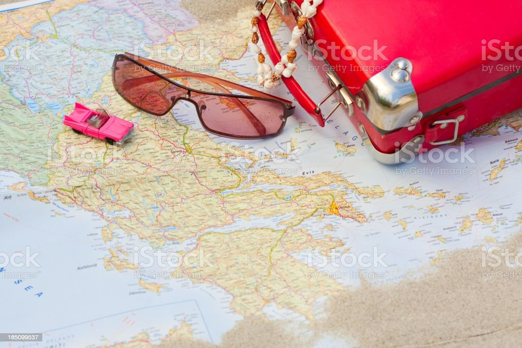 Miniature pink car with sunglasses and red bag over a map royalty-free stock photo
