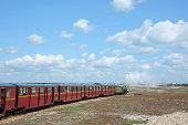 """The miniature light railway steam train travelling along the beach railway at Dungeness, Kent, UK"""