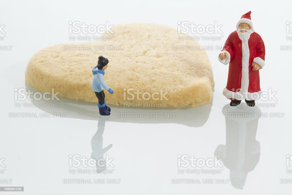 Miniature Santa Claus Child And Heart Shaped Cookie Stock Photo