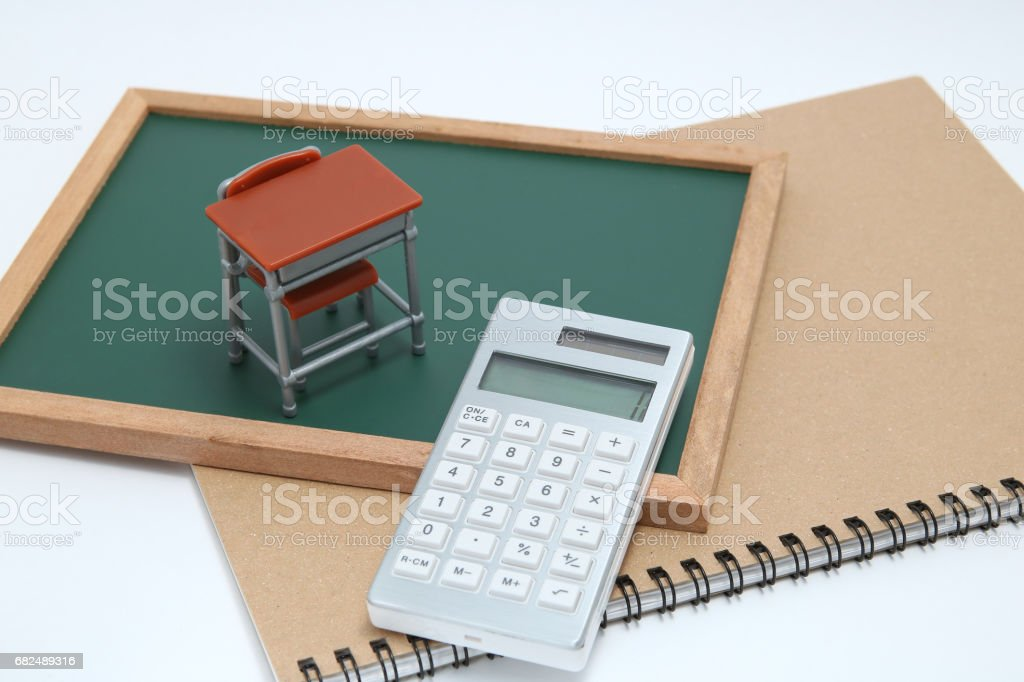 Miniature school desk, chalkboard and calculator on white background. royalty-free stock photo