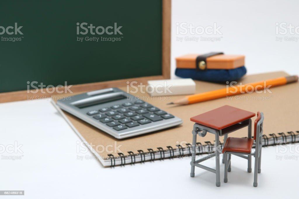 Minyatür okul Masası, chalkboard ve beyaz arka plan üzerinde hesap makinesi. royalty-free stock photo