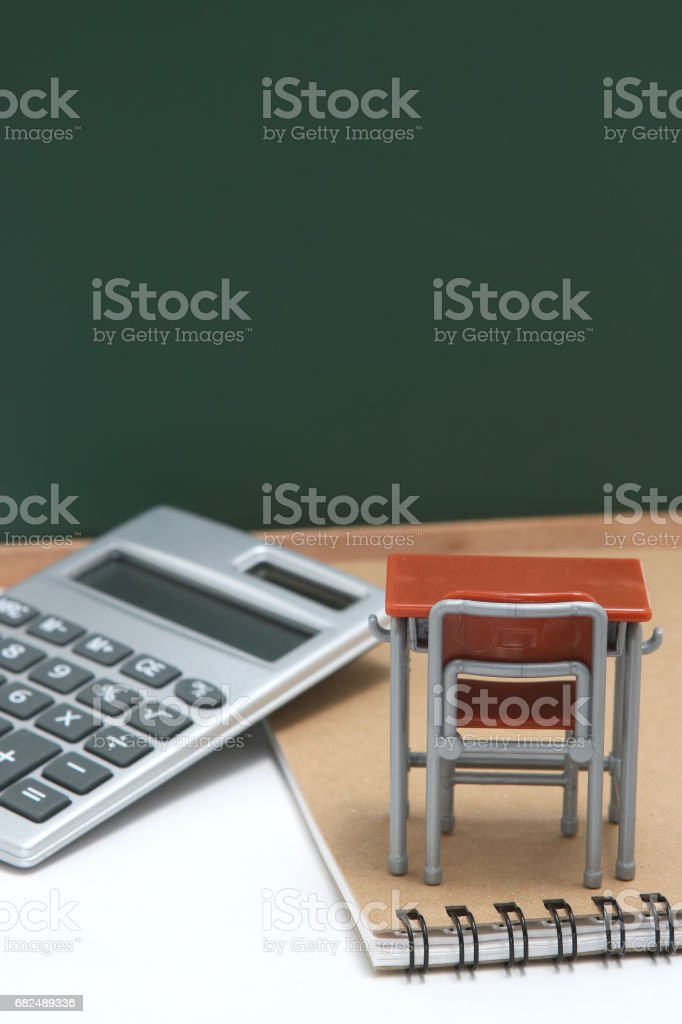 Miniature school desk, chalkboard and calculator on white background. Стоковые фото Стоковая фотография