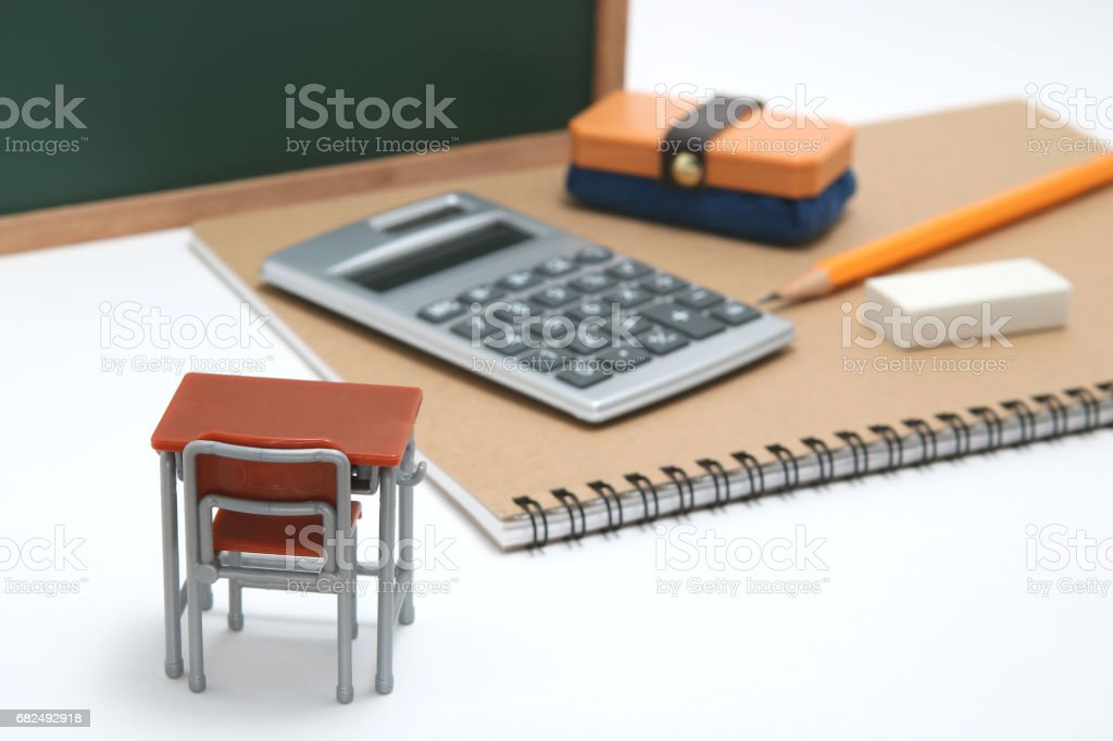 Miniature school desk, chalkboard and calculator on white background. foto stock royalty-free