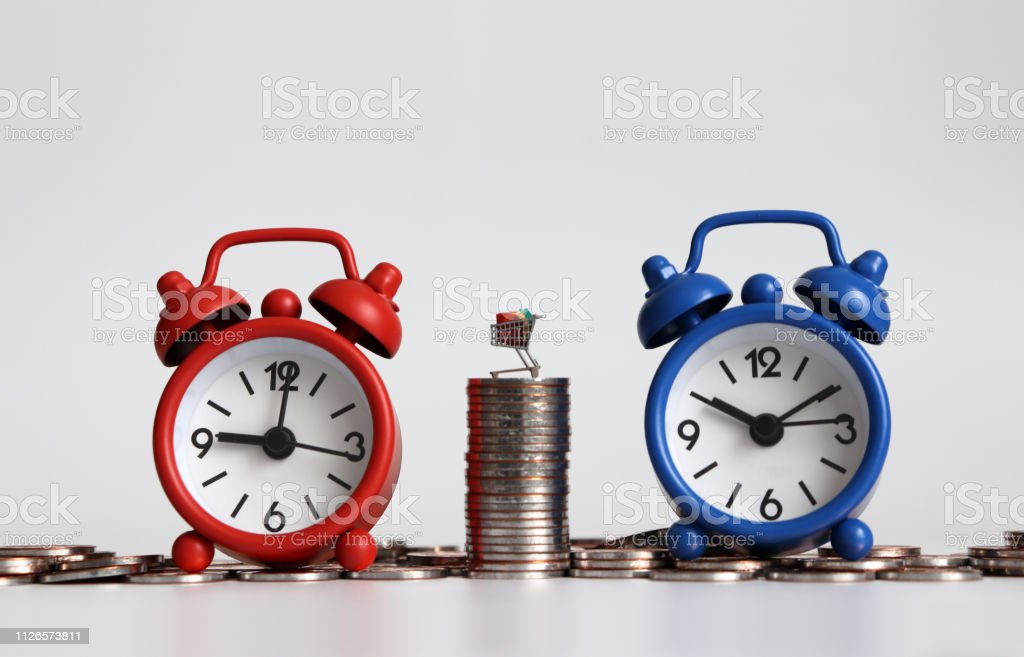 Miniature shopping cart on a pile of coins between two alarm clocks.