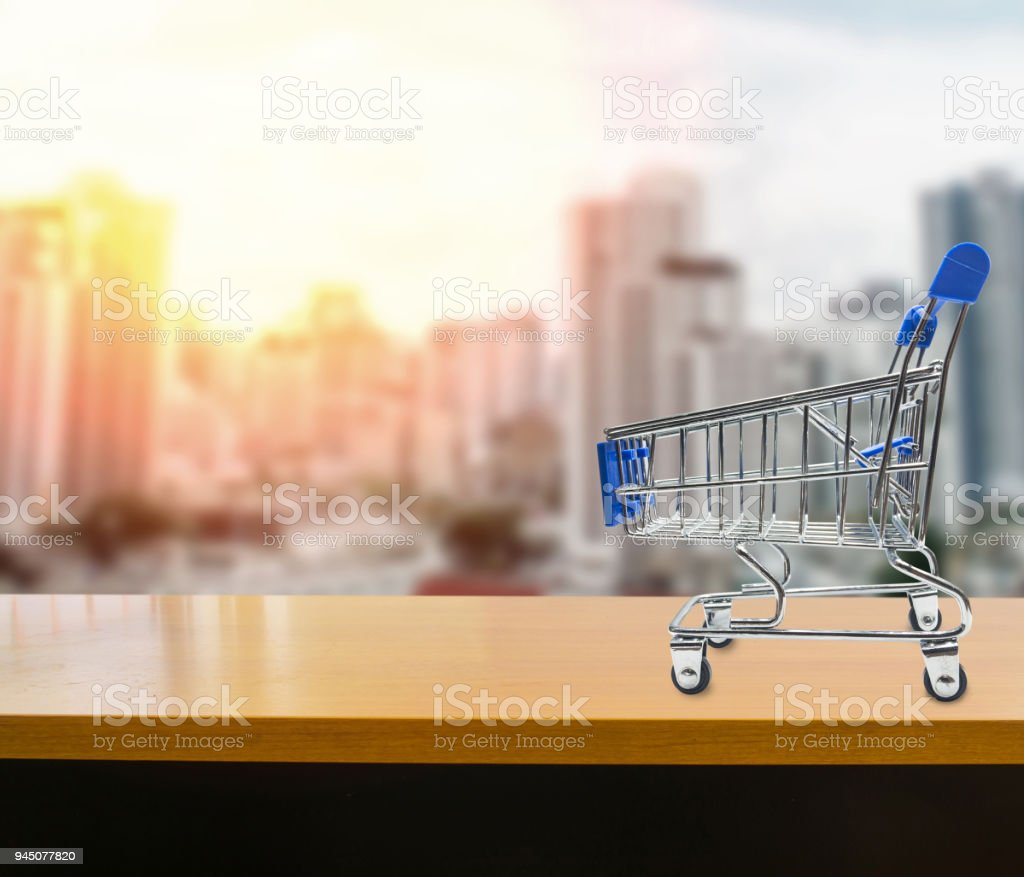 Miniature shopping cart on wood table on blurred abstract urban background stock photo