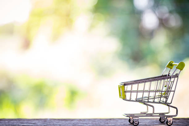 miniature shopping cart on wooden mock up stock photo