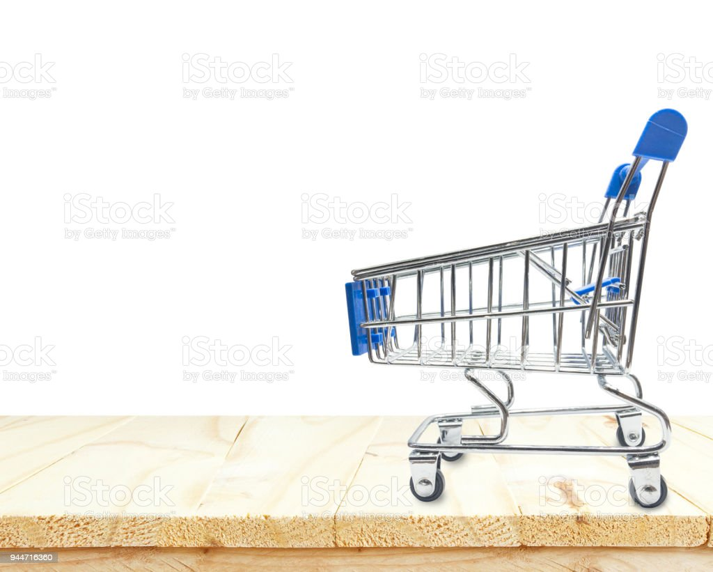 Miniature shopping cart on wooden table or mock up platform for interior decoration stock photo