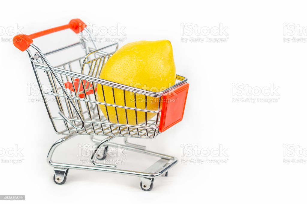 Miniature shopping cart with a lemon inside royalty-free stock photo