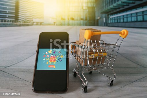Miniature shopping cart with gifts, shopping phone screen in front of shopping mall