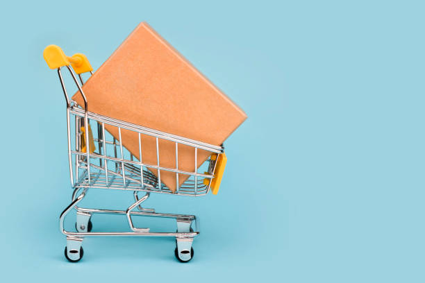 miniature shopping cart with large box isolated on blue background - icona supermercato foto e immagini stock