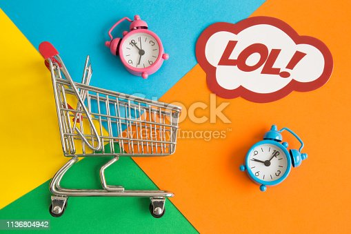 istock Miniature shopping trolley with alarm clocks and label with lol text on multicolored background abstract. 1136804942