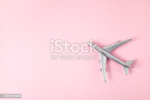 624266324 istock photo Miniature silver airplane. Travel tourism, airlines, low cost flights concept. Top view, flat lay. 1202578449