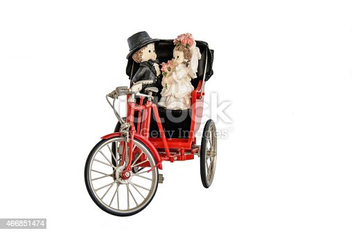 Miniature statue of cute bridal couple and red vintage oriental rickshaw cab, isolated on white