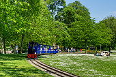 View of a Miniature Steam Train in the Pavilion Gardens Buxton, UK.  People can be seen riding on the train and sitting on the grass.