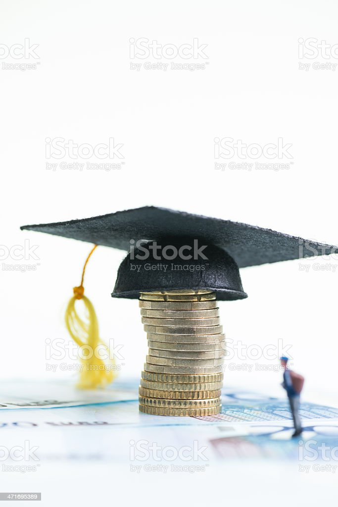 Miniature student looking at Mortarboard, Euro coins and banknotes royalty-free stock photo