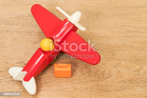 istock miniature suitcase and toy plane on table 1069433202
